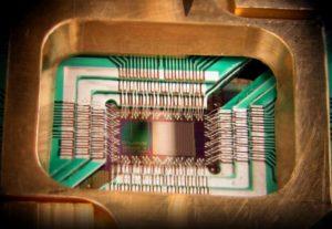 Zdjęcie chipa skonstruowanego przez D-Wave Systems Inc., zaprojektowanego do działania jako 128-kubitowy nadprzewodnikowy adiabatyczny procesor optymalizacji kwantowej