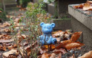 Zabawka dziecięca - niebieski miś - przy grobie dziecięcym, ilustracja do artykułu o raporcie NIK
