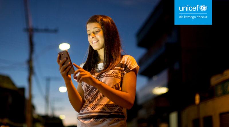 Dziewczynka ze smartfonem na tle miejskim, w górnym rogu logo INICEF Polska. Zdjęcie kampanii Przystań w sieci