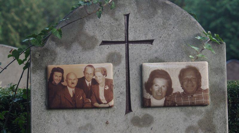 Nagrobek z dwoma zdjęciami rodzinnymi, po lewej rodzina czterosobowa, po prawie dwie osoby, w tym jedna o wiele starsza niż na zdjęciu po lewej. Po środku krzyż.