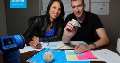 Kobieta i mężczyzna siedzący przy biurku, na stole kolorowe kartki. Mężczyzna trzyma papierowy samolocik. Po lewej logo UNICEF