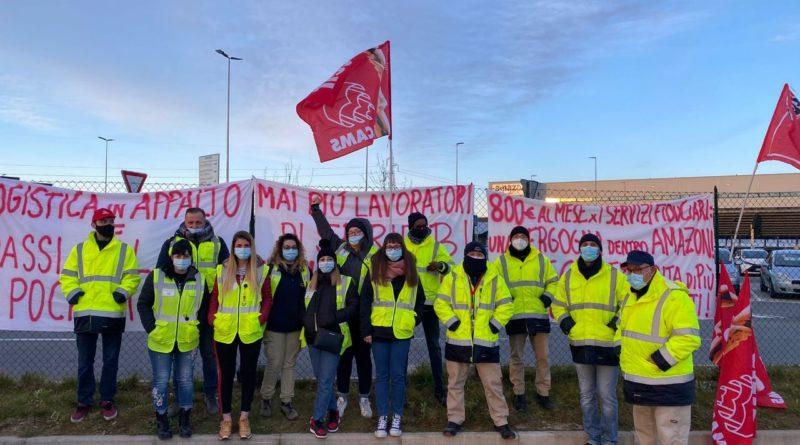 Strajkujący pracownicy Amazona pozują w grupie przed miejscem pracy