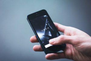 Aplikacja Ubera w telefonie trzymanym przez kogoś