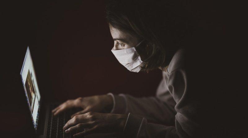 Kobieta w maseczce ochronnej siedząca w ciemnym pomieszczeniu, pisząca na laptopie.