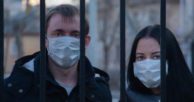 Dwoje młodych ludzi w maseczkach ochronnych, stoją na wolnym powietrzy, zasłonięci kratami, smutni