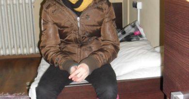 Biednie ubrane dziecko w zimowej kurtce siedzi na łóżku, w tle kaloryfr