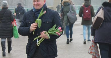Bartłomiej Wróblewski na ulicy, w zimnie, rozdaje tulipany w Dzień Kobiet