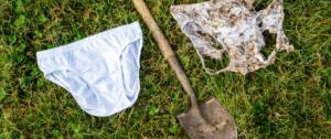 Dwie pary majtek na trawniku - jedna biała i nowa, druga przegniła i ze śladami ziemi. Po środku szpadel.