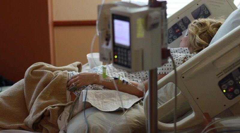 Kobieta w ciąży podczas pobytu w szpitalu, leżąca na łóżku i podłączona do kroplówek i aparatury