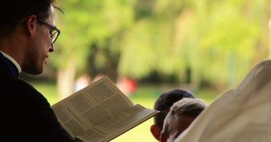 Ksiądz z Biblią modlący się nad głowami kilkuletnich chłopców