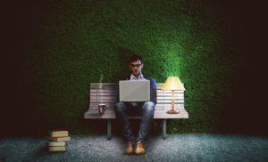 męzczyzna z laptopem na ławce, obok kawa i lampka biurkowa, na pierwszym planie książki ustawione w niewielki stosik