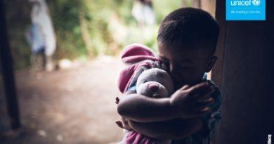 skulone w kąciku dziecko z zabawką, w prawym górnym rogu logo unicef